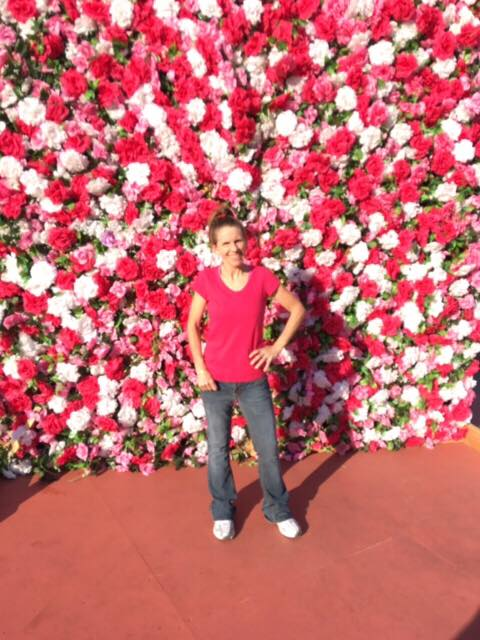 House Manager Kelly in front of a Wall of roses