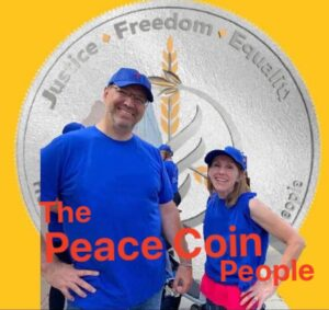 image of chris and kelly watkins in front of a big silver PeaceCoin