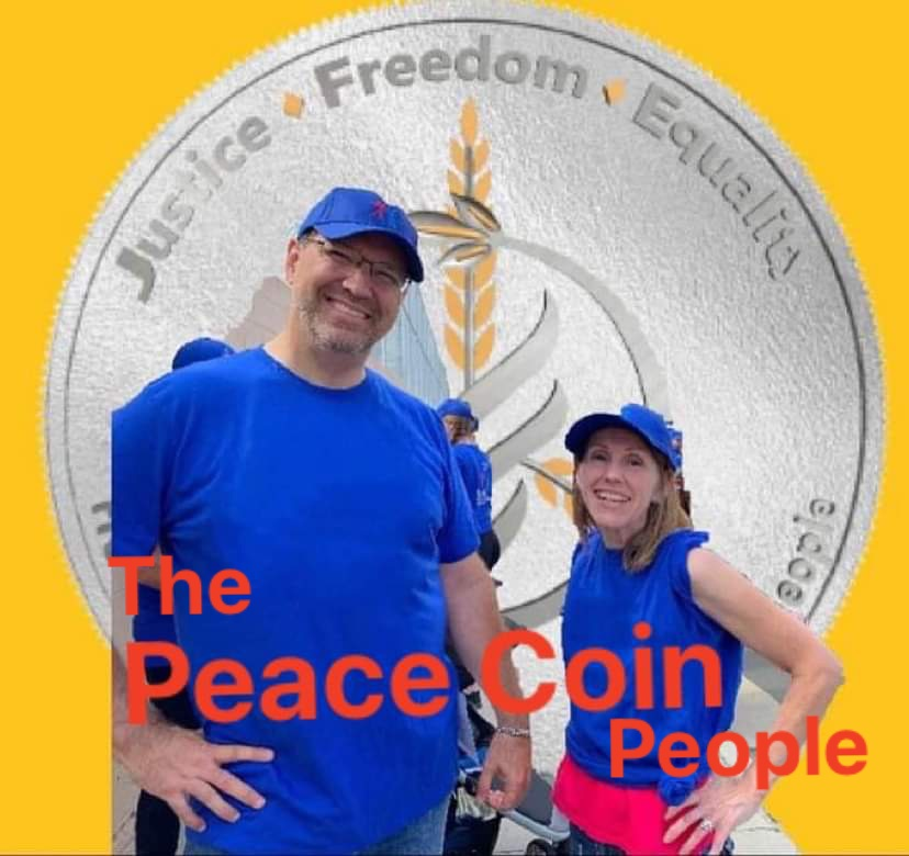 the peacecoin people, chris and kelly watkins pictured in front of a silver peace coin
